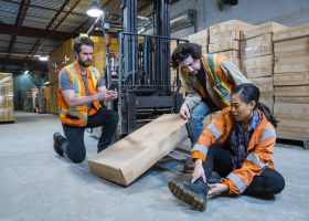 An industrial warehouse workplace safety topic. A worker injured falling or being struck by a forklift.